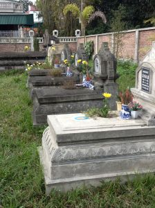 Graves in a family cemetery are cleaned and graced with flowers and incense for Têt.