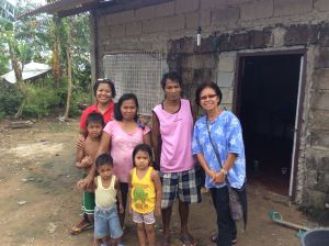May, Neneng and her family and Lina in front of the repaired house.  The top two rows of blocks are new.