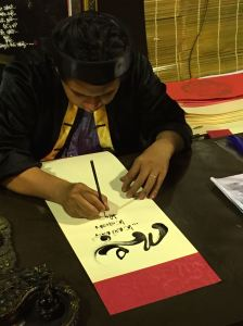 A young calligrapher writes a traditional New Year greeting.