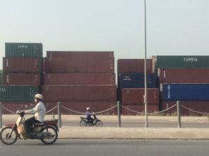 Containers line both sides of the road near the Dong Nai River.