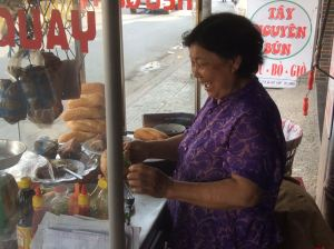 Mama Hung prepares a sandwich at her streetside stall.