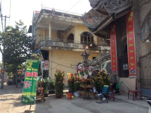 Pots of multicolored orchids stand by the gate of a temple, and red banners greet the New Year.