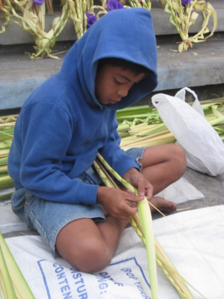 Boy weaving palaspas